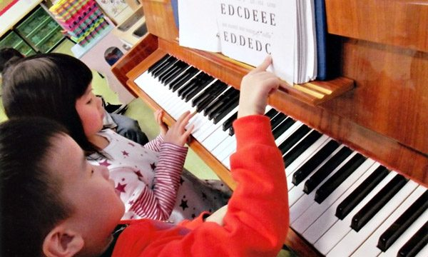 Music program: children learning to play the piano